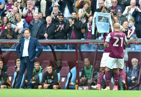 Gabriel Agbonlahor of Aston Villa scores the opening goal 1-0 and celebrates by holding up a shirt wishing a fellow player well as Manager Leonid Slutsky of Hull City looks on
