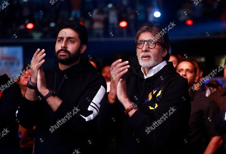 Bollywood star Amitabh Bachchan, right, along with his son Abhishek Bachchan cheer as they watch the Indian boxing match between WBO Asia-Pacific Super Middleweight champion Vijender Singhand WBO Oriental Super Middleweight champion of China Zulpikar Maimaitiali in Mumbai, India