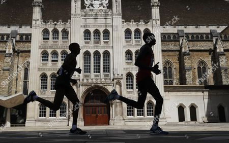 Daniel Kinyua Wanjiru (R) of Kenya and Alphonce Felix Simbu of Tanzania pass the Guild Hall during men's Marathon race at the London 2017 IAAF World Championships in London, Britain, 06 August 2017.