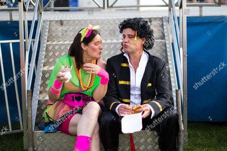 Stock Picture of A man dressed as Adam Ant eats a burger