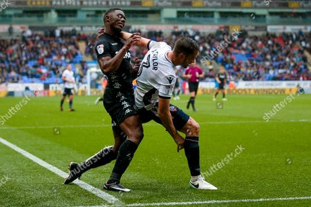 Leeds United forward Hadi Sacko (24) is stopped by Bolton Wanderers defender Andy Taylor (3)  during the EFL Sky Bet Championship match between Bolton Wanderers and Leeds United at the Macron Stadium, Bolton
