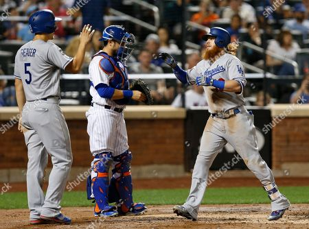 Corey Seager, Justin Turner, Travis' d'Arnaud Los Angeles Dodgers' Corey Seager (5), greets te Dodgers' Justin Turner (10) after scoring on Turner's second inning, three-run, home run in a baseball game against the New York Mets, in New York. Mets catcher Travis d'Arnaud is between the pair