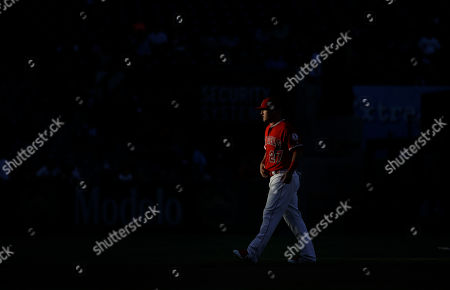 Stock Picture of Los Angeles Angels' Mike Trout walks through the shaft of light as he warms up before the team's baseball game against the Baltimore Orioles, in Anaheim, Calif