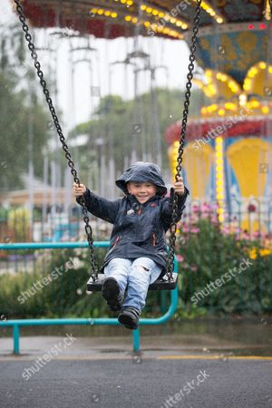 Stock Photo of Alex Cox not put out by the torrential downpours  on Tuesday August 8th by still having a fun in the rain at Wicksteed Park in Kettering