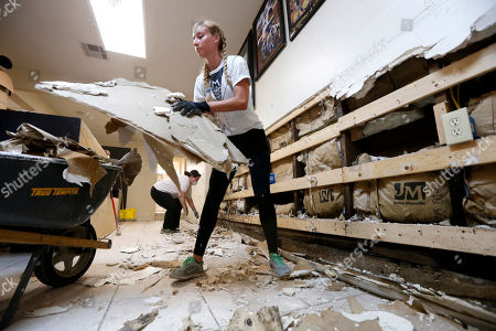 Pre-med studentsDanielle Ziemba, foreground, and Lorena Garcia, from the Miami Medical Team, help gut the Zulu Social Aid & Pleasure Club Store, which flooded during rain storms this past weekend, in New Orleans