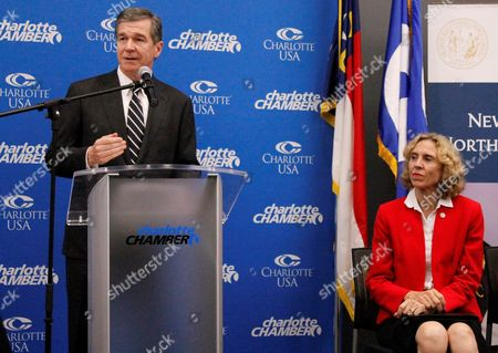 North Carolina Gov. Roy Cooper addresses an audience as Charlotte Mayor Jennifer Roberts listens to his remarks in Charlotte, N.C., on . Cooper announced that Allstate Insurance Co. is planning to double its workforce in the state by adding 2,250 new jobs by 2020