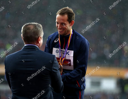 Renaud Lavillenie of France receives his Bronze medal  from retried polevaulter Sergey Bubka during the Men's Pole Vault medal ceremonies