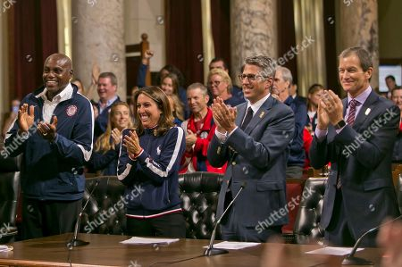 Stock Image of Carl Lewis, Janet Evans, Casey Wasserman, Gene Sykes Olympic champions Carl Lewis, left, and Janet Evans, who are part of a private committee behind the bid, join Casey Wasserman, LA 2028 chairman, and LA 2028 CEO Gene Sykes clap after City Council voted 12-0 to endorse documents at the heart of its plan to stage the Summer Olympics for the third time since 1932, in Los Angeles. The contract outlines Los Angeles' financial responsibility in hosting the Games, although a budget for the proposed 2028 Games has not been completed. The vote took place less than two weeks after the city announced an agreement with international Olympic leaders ceding the 2024 Games to rival Paris, while opening the way for Los Angeles to host the 2028 Games