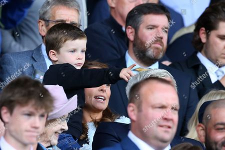 Stock Photo of Klay Rooney in the arms of his mum Coleen points as Wayne Rooney makes his second Premier League debut for Everton