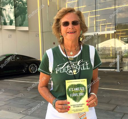 """Former New York Jets scout Connie Carberg poses with a recently released book, """"X's And O's Don't Mean I Love You,"""" outside the Jets practice facility in Florham Park, N.J., . How she helped deliver the sack-dancing Mark Gastineau to the Jets is just one of the many fascinating behind-the-scenes tales told by Carberg and author Elisabeth Meinecke. Gastineau went on to become one of the Jets' best and most popular players _ and helped cement Carberg's place in NFL history as the league's first female scout"""