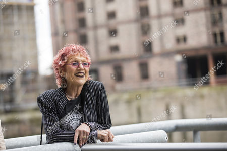 Stock Picture of Judy Chicago standing infront of her works 'Fixing a Hole' mural by The Titanic Hotel in Liverpool