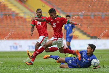 Osvaldo Ardiles Haay, Rattanakorn Maikami Indonesia's Osvaldo Ardiles Haay, left, is tackled by Thailand's player Rattanakorn Maikami, right, during the soccer match at the South East Asian Games in Shah Alam, Malaysia on