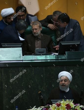 Iranian President Hassan Rouhani, bottom, speaks on his proposed cabinet while parliament speaker Ali Larijani, above center, listens to a group of lawmakers in a session of parliament, in Tehran, Iran, . Iran's president issued a direct threat to the West on Tuesday, claiming his country is capable of restarting its nuclear program within hours ? and quickly bringing it to even more advanced levels than in 2015, when Iran signed the nuclear deal with world powers