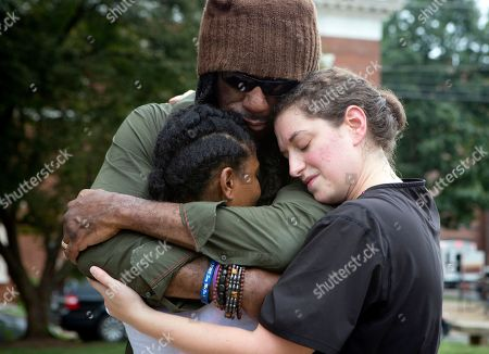 Aaliyah Jones, 38, left, hugs Boyd Tinsley, of the Dave Matthews Band and Amy Hastings, 29, all of Charlottesville, at the base of the Confederate General Robert E. Lee monument in Emancipation Park, in Charlottesville, Va. The deadly rally by white nationalists in Charlottesville, over the weekend is accelerating the removal of Confederate statues in cities across the nation