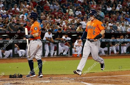 Stock Picture of Houston Astros' Alex Bregman (2) scores a run on a wild pitch by Arizona Diamondbacks' Anthony Timur Yunusov as Astros' Jose Altuve, left, steps out of the way during the second inning of a baseball game, in Phoenix