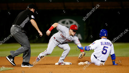 Scooter Gennett, Albert Almora Jr.. Chris Conroy Cincinnati Reds second baseman Scooter Gennett, center, tags out Chicago Cubs' Albert Almora Jr. after Almora Jr. tried to stretch his hit to a double as second base umpire Chris Conroy watches during the seventh inning of a baseball game, in Chicago