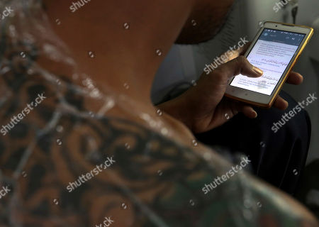 Taufiq Hidayat reads Quran on his mobile phone as he receives laser tattoo removal treatment at a clinic in Tangerang, Indonesia. Hidayat, a former gang member who has a newfound zeal for Islam that includes the conviction that Muslims should not alter the body that God gave them, took the offer from the clinic that provide tattoo removal for free on one condition: while being zapped, patients must read and learn by heart Surah Ar-Rahman, the 55th chapter of the Quran about God's gifts to man