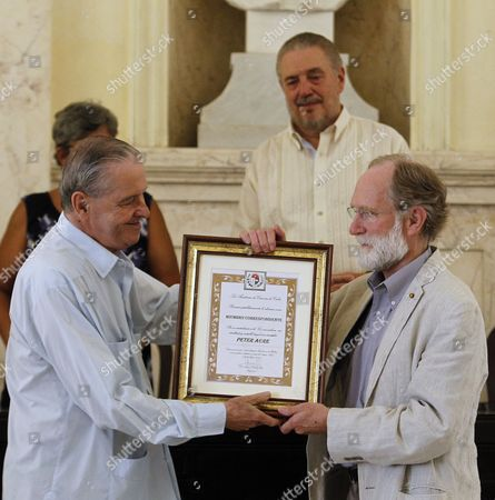 Stock Picture of Peter Courtland Agre (R),  2003 Chemistry Nobel Prize-winner of the US,  receives the title of Member of Cuba's Sciences Academy by President of the Cuba Sciences Academy, Ismael Clark (L),  next to Fidel Castro Diaz-Balart (behind), during a ceremony in Havana, Cuba, 16 August 2017.