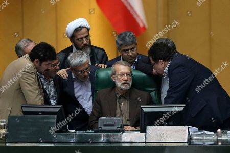 Iranian parliament speaker Ali Larijani, seated at center, talks with a group of lawmakers in a session of parliament to debate proposed cabinet by President Hassan Rouhani, in Tehran, Iran