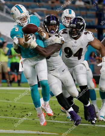 Za' Darius Smith, David Fales, Carl Davis Baltimore Ravens outside linebacker Za'Darius Smith (90) and defensive end Carl Davis (94), pressure Miami Dolphins quarterback David Fales (9), during the first half of an NFL preseason football game, in Miami Gardens, Fla