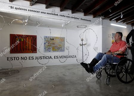 Prisoner Julian Gonzalez Vasquez, observes his work of art titled 'This is not justice, it is revenge' during the inauguration of the exhibition 'Lines of Freedom' in the La Paz Prison in Itagui, Colombia, 17 August 2017. The exhibition features the works of 38 inmates, and is sponsored in part by the National Penitentiary and Prison Institute (Inpec) with support from students from the University of Antioquia.