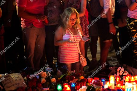 A woman prays at a memorial tribute of flowers, messages and candles to the victims on Barcelona's historic Las Ramblas promenade on the Joan Miro mosaic, embedded in the pavement where the van stopped after killing at least 13 people in Barcelona, Spain, . Spanish police on Friday shot and killed five people carrying bomb belts who were connected to the Barcelona van attack as the manhunt intensified for the perpetrators of Europe's latest rampage claimed by the Islamic State group