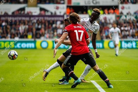 Tammy Abraham of Swansea City is tackled my Phil Jones and Daley Blind of Manchester United during the Premier League match between Swansea City and Manchester United at the Liberty Stadium, Swansea