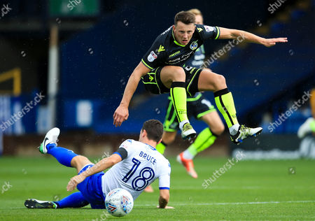 Ollie Clarke of Bristol Rovers hurdles a challenge from Alex Bruce of Bury