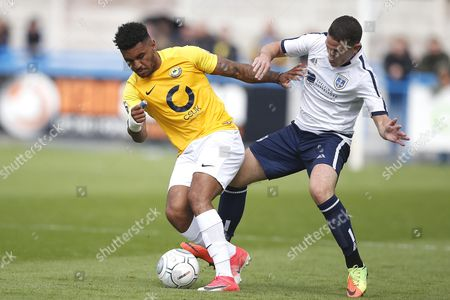 Torquay United player Jamie Reid competes with Guiseley player John Rooney during the English National League game between Guiseley and Torquay United at Nethermoor Park on Aug 19