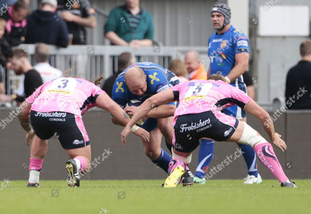 Brok Harris of Newport Dragons is tackled by Harry Williams of Exeter Chiefs and Jonny Hill of Exeter Chiefs during the Pre Season match between Exeter Chiefs and Newport Dragons at Sandy Park on August 19th 2017, Exeter, Devon.
