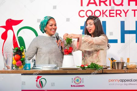 Stock Picture of Shelina Permalloo previous Master Chef winner helps Saliha Mahmood Ahmed, winner of Master Chef 2017 in a cooking demo at the Halal Food Festival