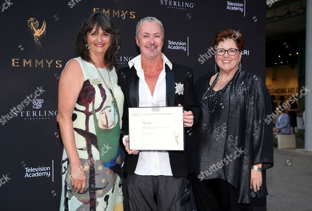"""Terry Ann Gordon, Sue Bub, Perry Meek Television Academy's Terry Ann Gordon, from left, costume designer Perry Meek, and Television Academy's Sue Bub pose with a plaque for his Emmy nomination for """"RuPaul's Drag Race: Oh. My. Gaga!"""" at the 11th annual """"Art of Television Costume Design"""" opening at the FIDM Museum & Galleries on the Park on in Los Angeles"""
