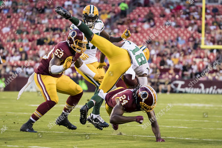 Washington Redskins cornerback Josh Norman (24) upends Green Bay Packers wide receiver Randall Cobb (18) during the NFL preseason game between the Green Bay Packers and the Washington Redskins at FedExField in Landover, Maryland