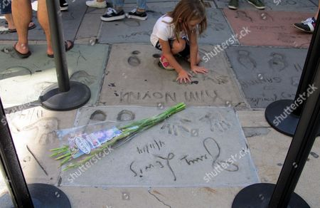 A girl places her hands in the cement imprints of a celebrity next to US actor Jerry Lewis cement imprints at TCL Chinese Theatre in Hollywood, California, USA, 20 August 2017.  US Entertainer and comedy legend Jerry Lewis has died at his home in Las Vegas, Nevada on 20 August 2017. He was 91. Lewis was best known for his work with Dean Martin and for raising money for muscular dystrophy research.