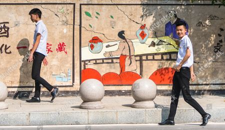 Two waiters from local baijiu bar walks on the street in front of the wall decorated with drawings of baijiu related themes in Maotai, Guizhou province, China, 19 August 2017. (issued 21 August) Moutai is a brand of baijiu, a distilled Chinese liquor (spirit), made in the town of Maotai in China's Guizhou province. Produced by the state-owned Kweichow Moutai Company, the beverage is distilled from fermented sorghum and now comes in several different varieties.