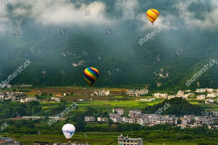 Balloons fly over the valley between Zunyi and Maotai town, Guizhou province, China, 19 August 2017. (issued 21 August) Moutai is a brand of baijiu, a distilled Chinese liquor (spirit), made in the town of Maotai in China's Guizhou province. Produced by the state-owned Kweichow Moutai Company, the beverage is distilled from fermented sorghum and now comes in several different varieties.