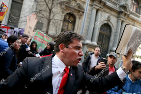 Evangelical pastor Javier Soto holds a bible as he chants in protest against Chile's Constitutional Court decision to uphold a measure that would end the country's absolute ban on abortions, in Santiago, . The court's vote accepts the constitutionality of a measure to legalize abortions when a woman's life is in danger, when a fetus is not viable and in cases of rape. Congress recently approved the bill and President Michelle Bachelet has said she will sign it into law