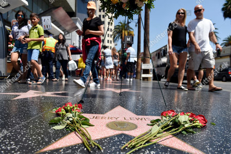 Pedestrians walk past Jerry Lewis' star following a memorial wreath ceremony for the late comedy icon on the Hollywood Walk of Fame, in Los Angeles. Lewis died at 91 on Sunday in Las Vegas