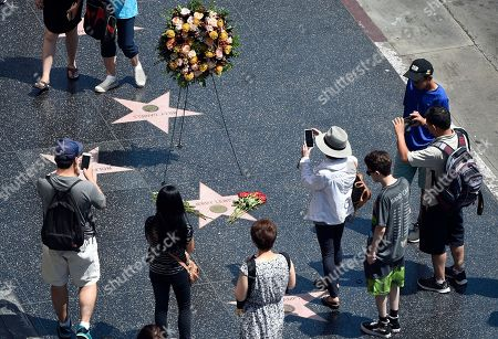 Onlookers gather around a memorial wreath for the late comedy icon Jerry Lewis at his star on the Hollywood Walk of Fame, in Los Angeles. Lewis died on Sunday in Las Vegas. He was 91