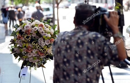 A cameraman films a memorial wreath for the late comedian and civil rights pioneer Dick Gregory following a ceremony at his star on the Hollywood Walk of Fame, in Los Angeles. Gregory died at 84 on Saturday, in Washington, D.C