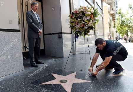 Leron Gubler, Davit Belyan Davit Belyan, right, lays down a memorial wreath for late comedian and civil rights pioneer Dick Gregory as Hollywood Chamber of Commerce Chairman and CEO, Leron Gubler looks on during a ceremony at Gregory's star on the Hollywood Walk of Fame, in Los Angeles
