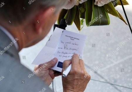 Hollywood Chamber of Commerce Chairman and CEO Leron Gubler writes an inscription for a memorial wreath for the late comedian and civil rights pioneer Dick Gregory during a ceremony at his star on the Hollywood Walk of Fame, in Los Angeles. Gregory died Saturday, Aug. 19, 2017, at 84 in Washington, D.C