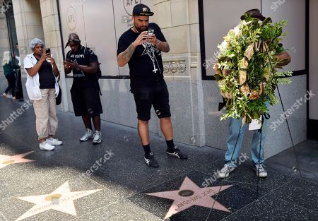 Stock Photo of Jonathan Sheppard, center, of Los Angeles takes a picture of a memorial wreath for the late comedian and civil rights pioneer Dick Gregory following a ceremony at his star on the Hollywood Walk of Fame, in Los Angeles. Gregory died at 84 on Saturday in Washington, D.C
