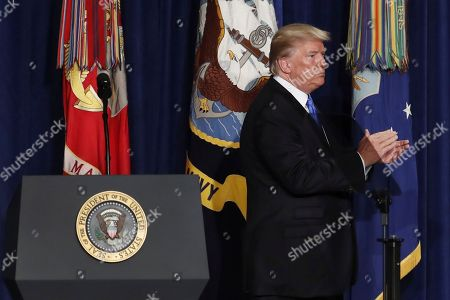President Donald Trump applauds as he walks off the dais after speaking at Fort Myer in Arlington Va., during a Presidential Address to the Nation about a strategy he believes will best position the U.S. to eventually declare victory in Afghanistan