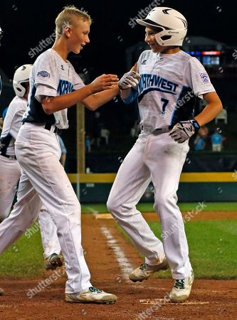 Walla Walla, Wash.'s Caiden Thomsen (7) celebrates with Andrew Hall as he crosses home plate after hitting a solo-home run during the fifth inning of an elimination baseball game against Fairfield, Conn., in United States pool play at the Little League World Series tournament in South Williamsport, Pa., . Connecticut won 14-6