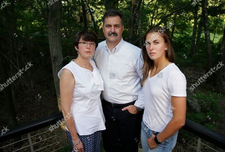 """Family members of 18-year-old murder victim Andrew Oneschuk, from the left, mother Chris, father Walter, and sister Emily, stand for a portrait at their home in Wakefield, Mass. Devon Arthurs, 18, co-founder of the neo-Nazi group Atomwaffen, which is German for """"atomic weapon,"""" was arrested on murder charges in the shooting death of two roommates, including Oneschuk, in Florida, in May of 2017"""