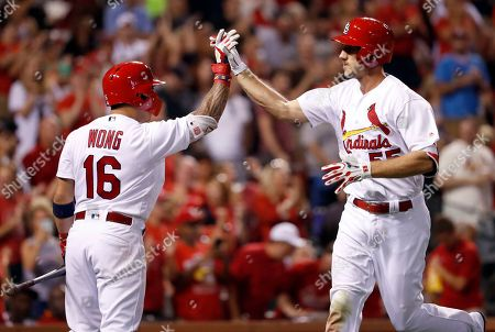 St. Louis Cardinals' Stephen Piscotty, right, is congratulated by teammate Kolten Wong after hitting a solo home run during the fourth inning of a baseball game against the San Diego Padres, in St. Louis