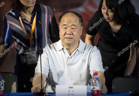 Stock Photo of Chinese Literature Nobel Prize winner Mo Yan, center, arrives for a panel discussion at the Beijing International Book Fair in Beijing, . The fair, which draws Chinese and international publishers, runs until Aug. 27