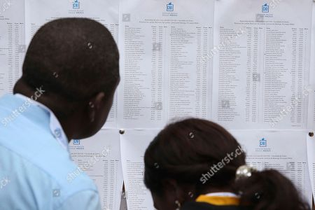 Voters check for their name on a voter register at a polling station in Luanda, . Defense Minister Joao Lourenco is the front-runner to succeed President Jose Eduardo dos Santos, who will step down after 38 years in power in an oil-rich country