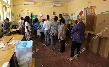 Voters queue to cast their votes at a polling station in presidential elections in Luanda, . Defense Minister, Joao Lourenco, is the front-runner to succeed President Jose Eduardo dos Santos, who will step down after 38 years in power in an oil-rich country